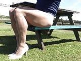 Public bench posing in tan pantyhose .