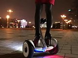 Hot girl driving gyroscooter in high heels and short skirt