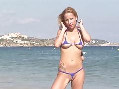 Gorąca blondynka mamuśki pozowanie na publicznej plaży w bikini string
