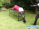 Leather clad master spanking whipping TGirl ass in garden