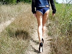 Denim shorts and high heels walking on a field road