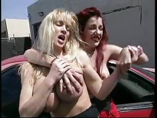 Redhead and blond fighting by the car