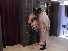 2 slaven in kunststof regenjas en rubber - aan elkaar gebonden