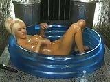 Kerrie Lee in a paddling pool covered in oil