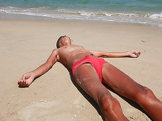 red speedo TYR pissing on the beach