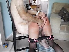 Rear view of granny spanked and hooked by two masters